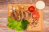 Grilled steak with vegetables on a wooden board.