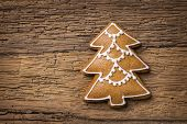 Christmas tree gingerbread cookie on a brown background