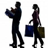 one  couple woman man christmas present shopping in silhouette studio isolated on white background