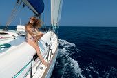 Young lady relaxing on the moving yacht in sea at sunny day