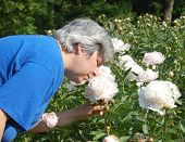 Middle Aged Woman Smelling Flower