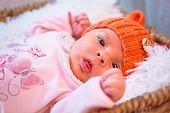 Newborn baby girl in orange knitted hat