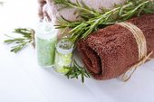 Branches of rosemary, towels and bottle with sea salt on color wooden background. Rosemary spa concept