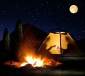 Camp shines at night. The campfire in the front as the symbol of adventure and romantic.