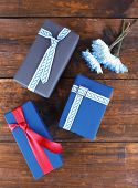 Three present boxes with flowers on wooden background