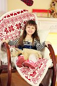 Little girl sitting in rocking chair near fireplace