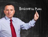 Portrait of a businessman writing Business Plan on a blackboard