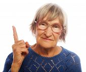 happy senior woman pointing upwards isolated on white background