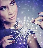 Portrait of beautiful woman with festive luxury makeup holding on hands big glowing snowflake on snowy background, Christmas celebration concept