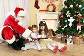 Santa Claus giving  present to  little cute girls near  fireplace and Christmas tree at home