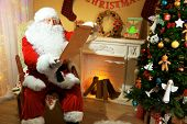 Santa Claus sitting with list of presents in comfortable chair near fireplace at home