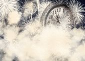 New Year's at midnight - old clock on bokeh background of holiday lights and fireworks