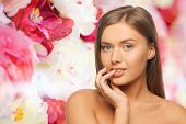 beauty, people and health concept - beautiful young woman touching her lips over pink floral background