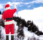 christmas, holidays and people concept - man in costume of santa claus writing something from back over snowy mountains background