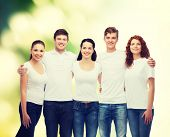 advertising, ecology, nature, friendship and people concept - group of smiling teenagers in white blank t-shirts over green background
