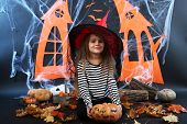 Little girl Witch in hat with pumpkins on Halloween decorations background