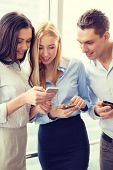 business and technology concept - smiling business team with smartphones in office