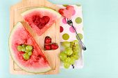 Fresh juicy watermelon slice  with cut out heart shape, filled fresh berries, on cutting board, on wooden background