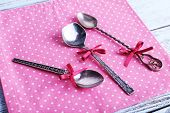 Metal spoons on pink polka dot napkin on wooden background
