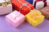 Pile of colorful gifts on purple background