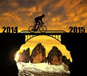 Cyclist riding across the bridge at sunset. In the background Tre Cime di Lavaredo. Forward to the New Year 2015