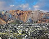 National Park Landmannalaugar in Iceland. Pieces of gray and black lava, sometimes covered with green moss. In the background -  orange and blue rhyolite mountains