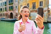 Closeup On Happy Young Woman Showing Thumbs Up And Making Selfie In Venice, Italy