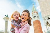 Portrait Of Happy Mother And Baby Against Campanile Di San Marco In Venice, Italy