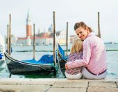 Portrait Of Happy Mother And Baby Sitting On Grand Canal Embankment In Venice, Italy