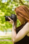 Side view of beautiful female photographer at the park