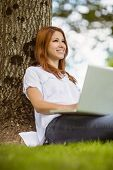 Pretty redhead smiling with her laptop in park