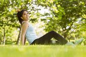 Side view portrait of healthy young woman sitting on grass in park