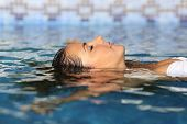 image of rest-in-peace  - Profile of a beauty relaxed woman face floating in water of a pool enjoying vacations - JPG