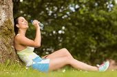 Fit brunette sitting against tree drinking water in the park