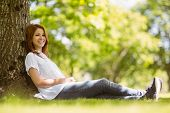 Pretty redhead sitting and smiling in park on a sunny day