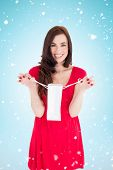 Stylish brunette in red dress holding shopping bag against blue background with vignette
