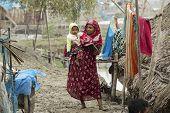 Woman takes care of her son, Mongla, Bangladesh.