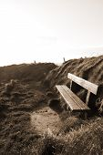 Bench On A Cliff Edge At Sunset In Sepia