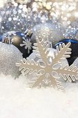 Christmas bauble background with snowflake decoration nestled in snow
