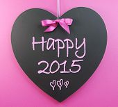 Happy New Year Greeting For 2015 Message On Heart Shape Blackboard Against A Pink Background.