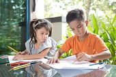Young pan asian boy with his curious younger sister enjoying drawing and coloring on paper in a home environment