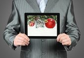 Man holds tablet PC with Christmas composition