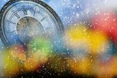 New Year's at midnight - old clock in snow on colorful bokeh background
