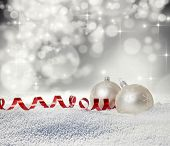 Christmas balls in snow on bokeh background