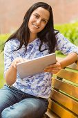 Smiling brunette sitting on bench using tablet in the park
