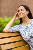 Happy brunette sitting on bench relaxing in the park