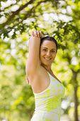 Happy brunette in sportswear stretching in the park