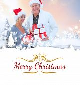 festive mature couple holding christmas gifts against border
