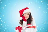 Unsure brunette in santa hat packing gifts against blue vignette