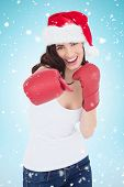 Festive brunette in boxing gloves punching against blue background with vignette
